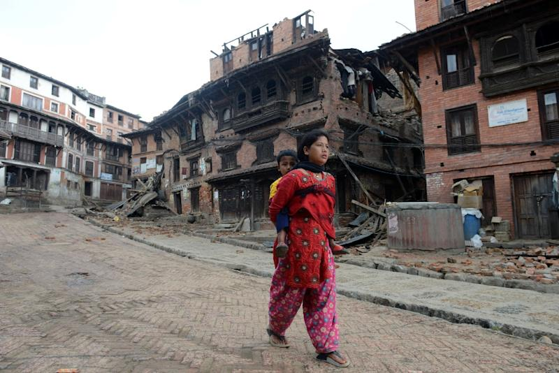 A woman carries a child next to collapsed houses in Bhaktapur, on the outskirts of Kathmandu, on April 27, 2015 (AFP Photo/Prakash Mathema)