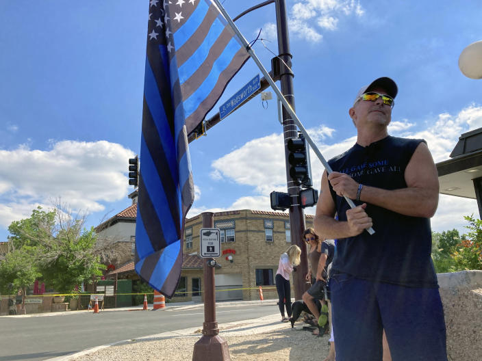 John Garrod, of Arvada, stands holding a blue line flag at the beginning of a line of about 30 police cars lined up for a procession in honor of the officer who was fatally shot in Arvada, Colo., on Monday, June 21, 2021. A gunfight between two men and police officers at a shopping district in a Denver suburb left an officer and one of the suspects dead, authorities said Monday. (AP Photo/Colleen Slevin)