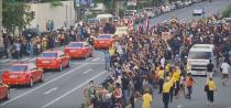 Social media video still of the royal motorcade carrying Thailand's Queen Suthida and Prince Dipangkorn driving past a group of anti-government demonstrators in Bangkok