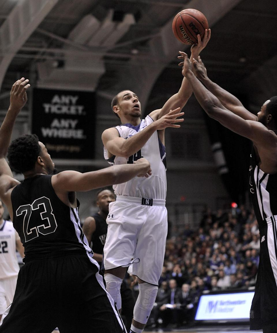 Northwestern's Tre Demps (14), goes up for a shot against Mississippi Valley State's Jeffery Simmons (5) and Latrell Love (23) during the first half of an NCAA college basketball game in Evanston, Ill., Sunday, Dec. 14, 2014. (AP Photo/Paul Beaty)