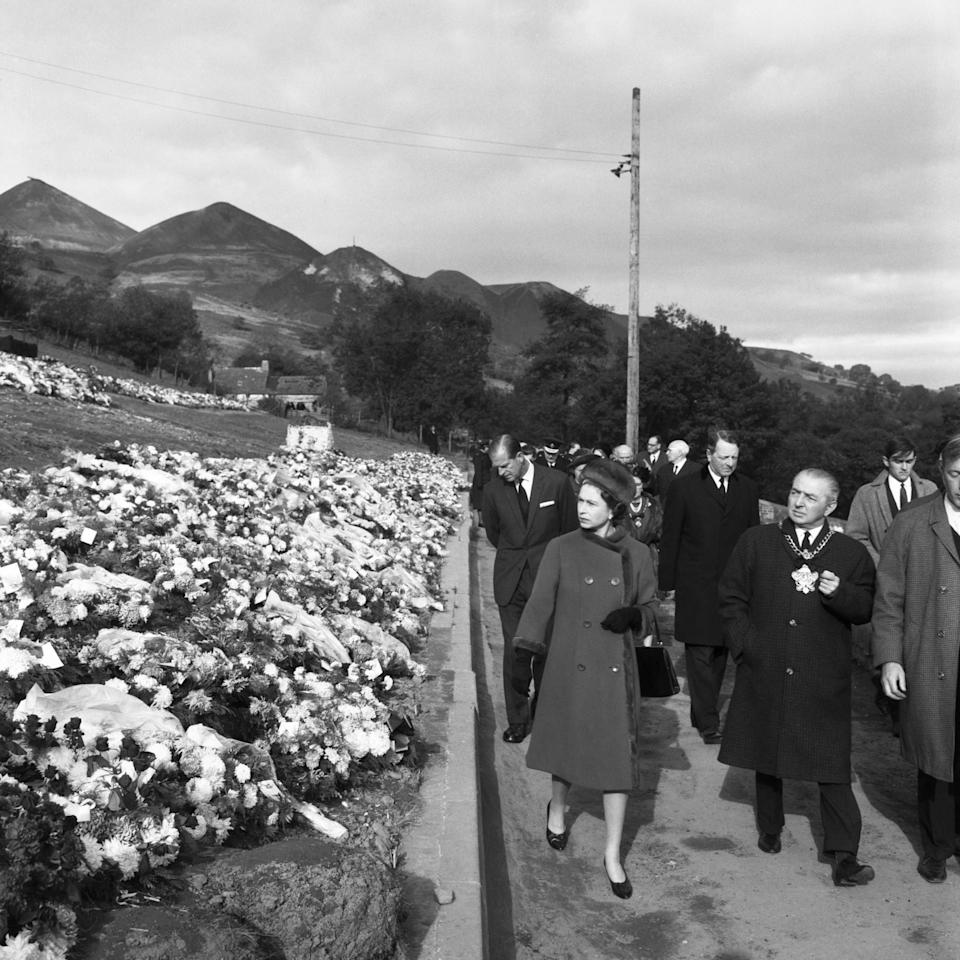 <p>The Duke of Edinburgh accompanies the Queen on a visit to the village of Aberfan, South Wales, to view a mass grave in the hillside cemetery of 82 of the 147 victims of the coal-tip avalanche. (PA Archive) </p>