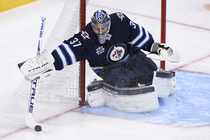Winnipeg Jets goaltender Connor Hellebuyck steers a shot by the Edmonton Oilers to the corner during the second period of an NHL hockey game Tuesday, Jan. 26, 2021, in Winnipeg, Manitoba. (Fred Greenslade/The Canadian Press via AP)