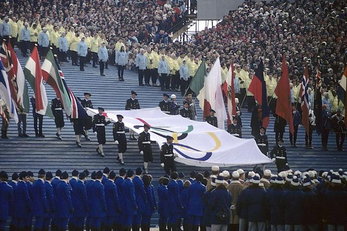 <p>Hosting over 60,000 people, the Olympic Stadium in Grenoble was only used for the Games and disassembled immmediately after. The torch was lit by 1964 silver medalist Alain Calmat.</p>