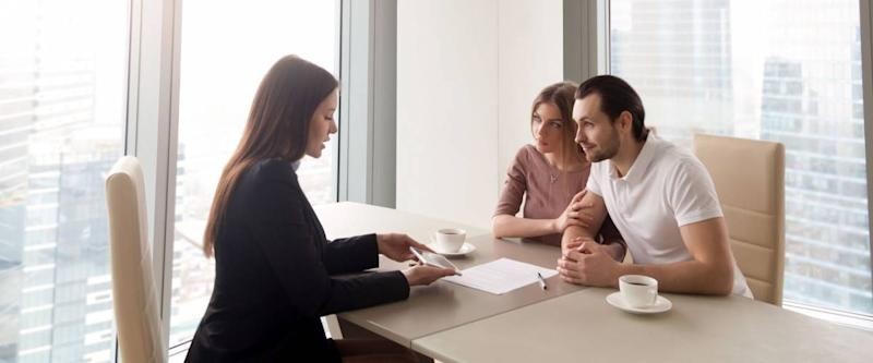 Young family couple meeting with bank worker to sign loan contract, discussing banking credit, personal insurance or mortgage investment, manager showing clients build project on tablet