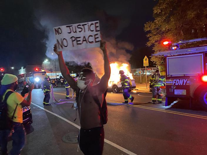No justice, no peace: a protester stands in front of a burning police car in Brooklyn: Richard Hall/The Independent