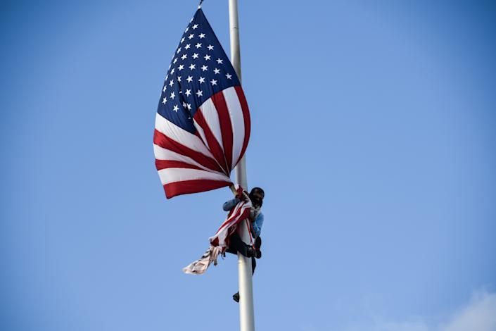 Puerto Rican environmental activist Tito Kayak climbs the pole in front of the capitol building to take down the flag of USA during the fifth day of protests calling for the resignation of Governor Ricardo Rossello in San Juan, Puerto Rico July 17, 2019. (Photo: Gabriella N. Baez/Reuters)