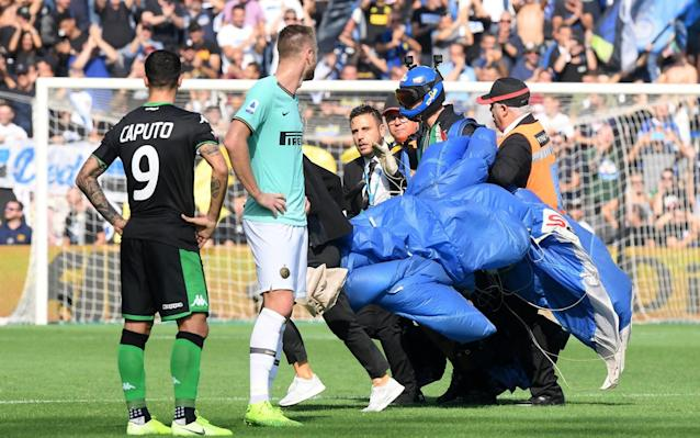The parachutist is led away after stopping the Inter vs Sassuolo match - REUTERS