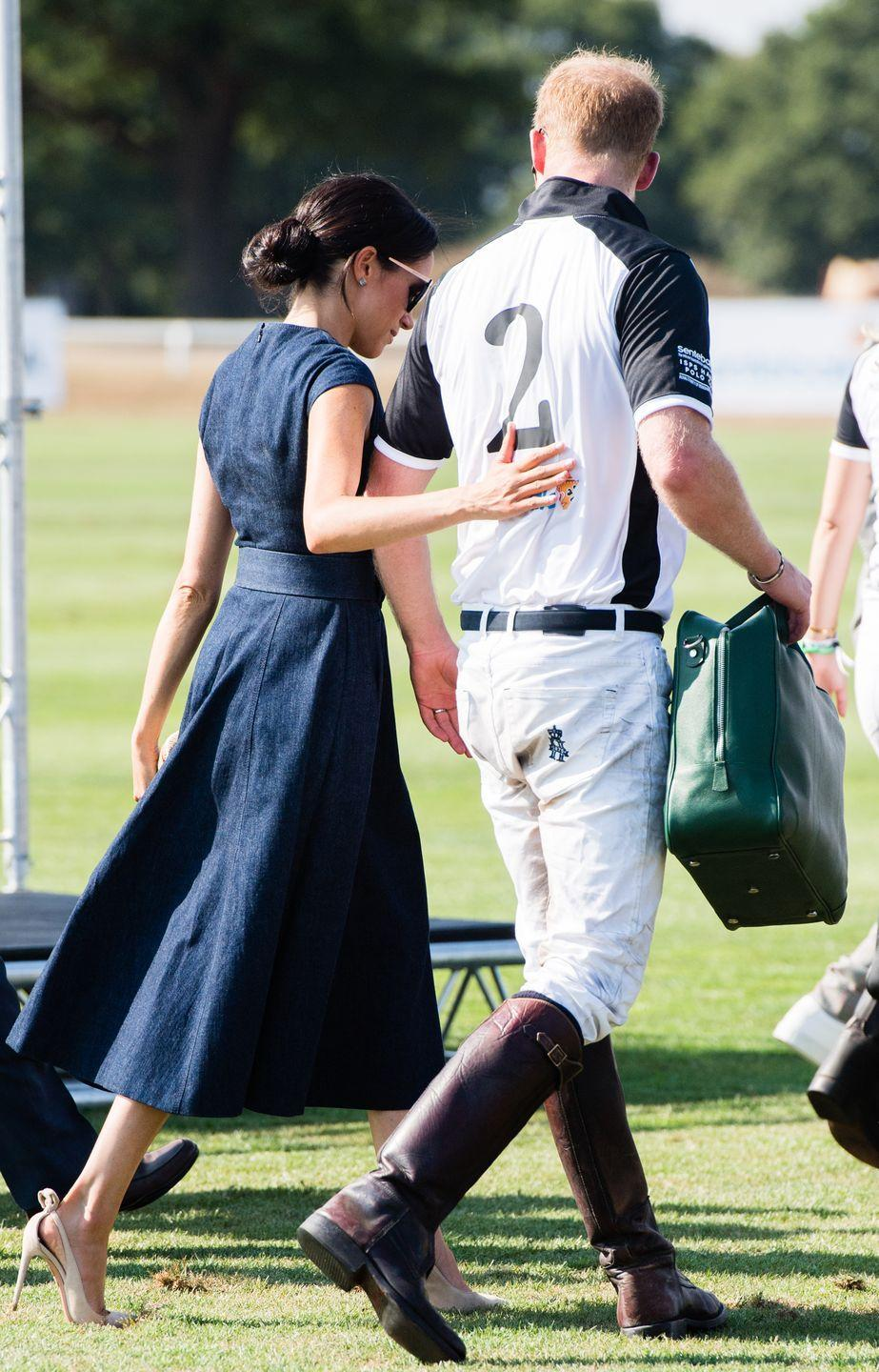 """<p>Following Prince Harry's polo match in July 2018, a <a href=""""https://www.elle.com/uk/fashion/celebrity-style/a22559039/meghan-markle-carolina-herrera-navy-blue-dress-polo/"""" rel=""""nofollow noopener"""" target=""""_blank"""" data-ylk=""""slk:Carolina Herrera-clad Meghan"""" class=""""link rapid-noclick-resp"""">Carolina Herrera-clad Meghan</a>was seen putting an affectionate hand on his back. Too cute! </p>"""