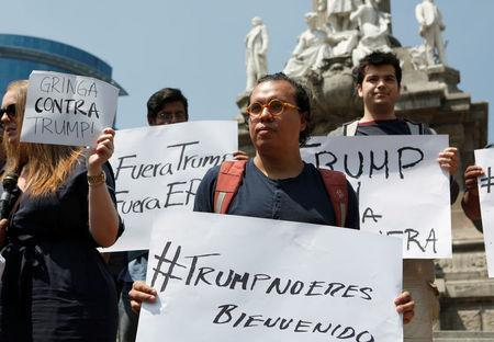 """Demonstrators hold placards during a protest against the visit of Donald Trump, at the Angel of Independence monument in Mexico City. The placards read """"Trump, you are not welcome,"""" and """"Trump out."""" REUTERS/Ginnette Riquelme"""