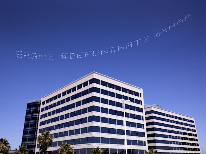 """SHAME #DEFUNDHATE #XMAP,"" a skytyped message by artist Cassils over the Geo Group Headquarters, a private prisons company, in Los Angeles on July 3. <span class=""copyright"">(Robin Black / In Plain Sight)</span>"