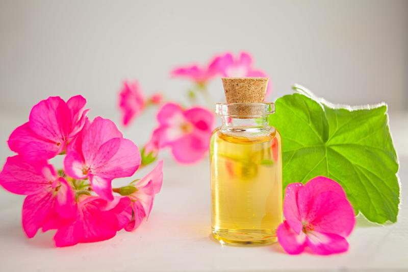 Bottle of yellow essential oil surrounded by geranium flowers.