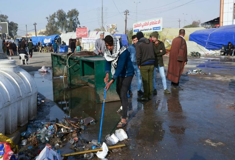 Iraqi demonstrators help with the clean-up in the main protest camp in the shrine city of Najaf after a night of violence blamed on supporters of populist cleric Moqtada Sadr