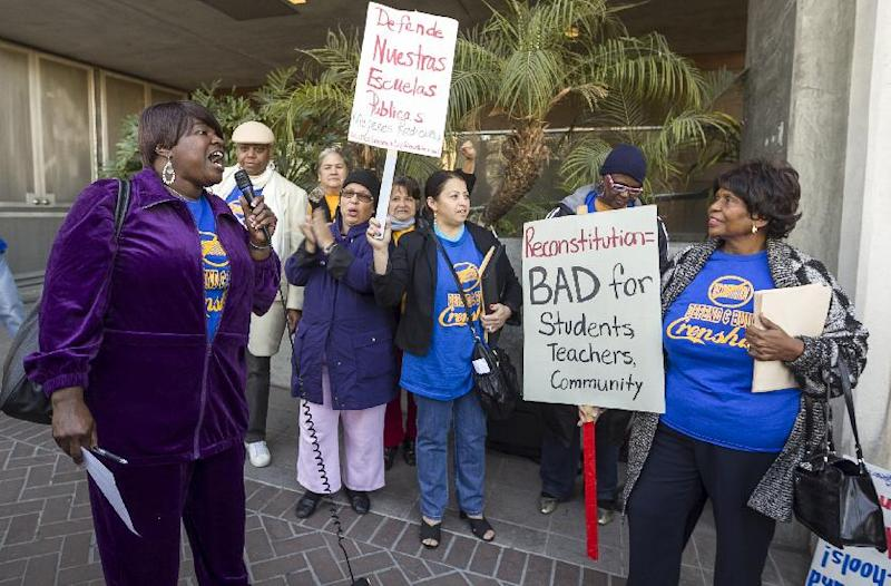 In this photo taken Tuesday, Jan. 15, 2013, parents, teachers and students of Crenshaw High School protest outside the Los Angeles Unified School District headquarters to try to stop the conversion of the school to a magnet program in Los Angeles Tuesday, Jan. 15, 2013. A backlash against drastic school reforms is growing across the nation. (AP Photo/Damian Dovarganes)