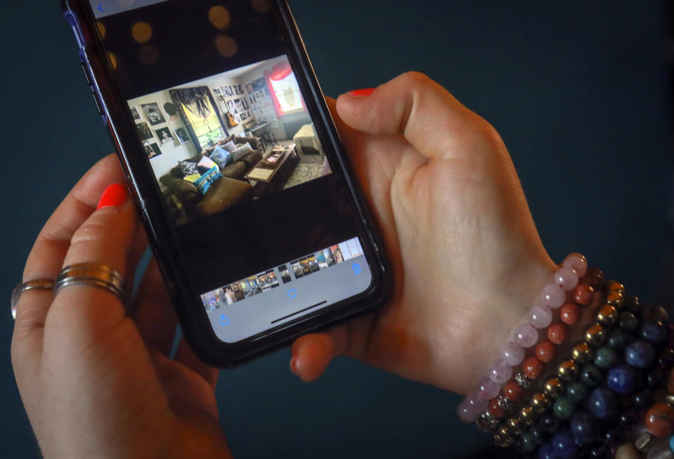 Rachel Berry shows a cellphone photo of her living room before a makeover with her art, Monday, July 6, 2020, in New York. Before the coronavirus pandemic, Berry worked as a bartender and waited tables, jobs that gave her enough time to work on her creative pursuits. But as New York City tries to reopen, there's concern that jobs for the city's creative class are no longer readily available. (AP Photo/Bebeto Matthews)