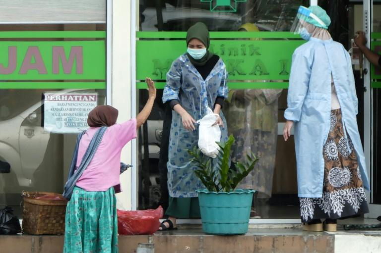 A food seller (L) gestures to health officials at a clinic in the Indonesian capital Jakarta