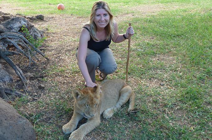 Angela Saurine patting a lion cub at Casela Bird and Nature Park in Mauritius. Photo: Supplied