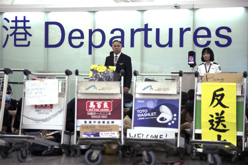 Airport security personnel look on as protesters using luggage trolleys to block the departure gates during a demonstration at the Airport in Hong Kong, Tuesday, Aug. 13, 2019. Protesters severely crippled operations at Hong Kong's international airport for a second day Tuesday, forcing authorities to cancel all remaining flights out of the city after demonstrators took over the terminals as part of their push for democratic reforms. (AP Photo/Vincent Thian)