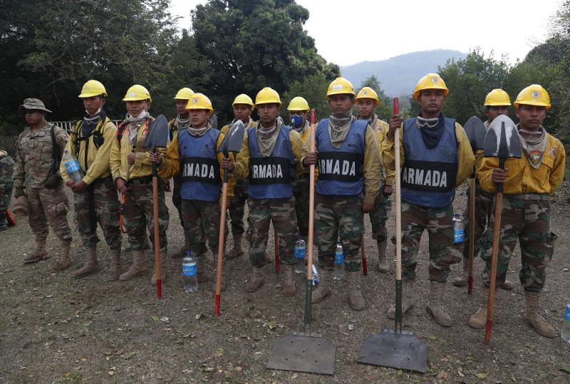 Soldiers line up as they get ready to help put out a forest fire in the Chiquitania Forest of Quitunuquina near Robore, Bolivia, Monday, Aug. 26, 2019. Bolivia has struggled to contain fires that swept through woods and fields. A U.S.-based aircraft, the B747-400 SuperTanker, is flying over devastated areas in Bolivia to help put out the blazes and protect forests. (AP Photo/Juan Karita)