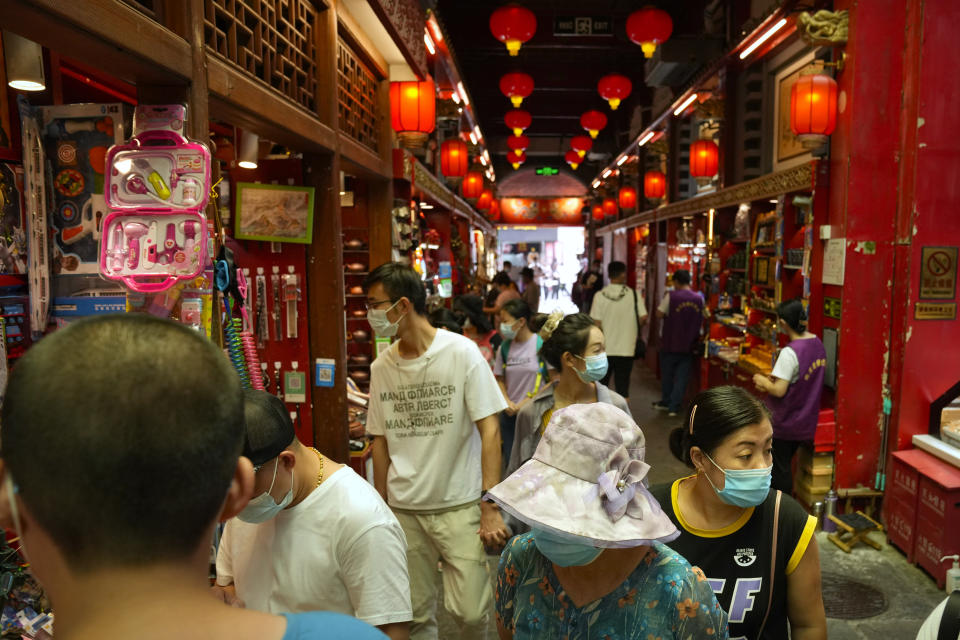 Visitors wearing face masks look at souvenir shops in a neighborhood popular with tourists in central Beijing, Tuesday, Aug. 3, 2021. From the Great Wall to the picturesque Kashmir valley, Asia's tourist destinations are looking to domestic visitors to get them through the COVID-19 pandemic's second year. With international travel heavily restricted, foreign tourists can't enter many countries and locals can't get out. (AP Photo/Mark Schiefelbein)