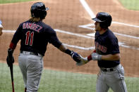 Cleveland Indians' Myles Straw is met by Jose Ramirez (11) after scoring a run in the first inning during a baseball game against the Texas Rangers in Arlington Texas, Sunday, Oct. 3, 2021. (AP Photo/Matt Strasen)