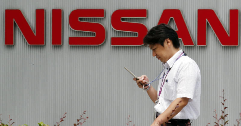 A man walks outside Nissan Motor Co.,'s head office in Yokohama, near Tokyo, Thursday, July 25, 2013. Nissan's quarterly profit jumped 14 percent to 82 billion yen ($820 million) as better sales in the U.S. and a perk from a favorable exchange rate offset damage from a sales slump in China and Europe. (AP Photo/Koji Sasahara)