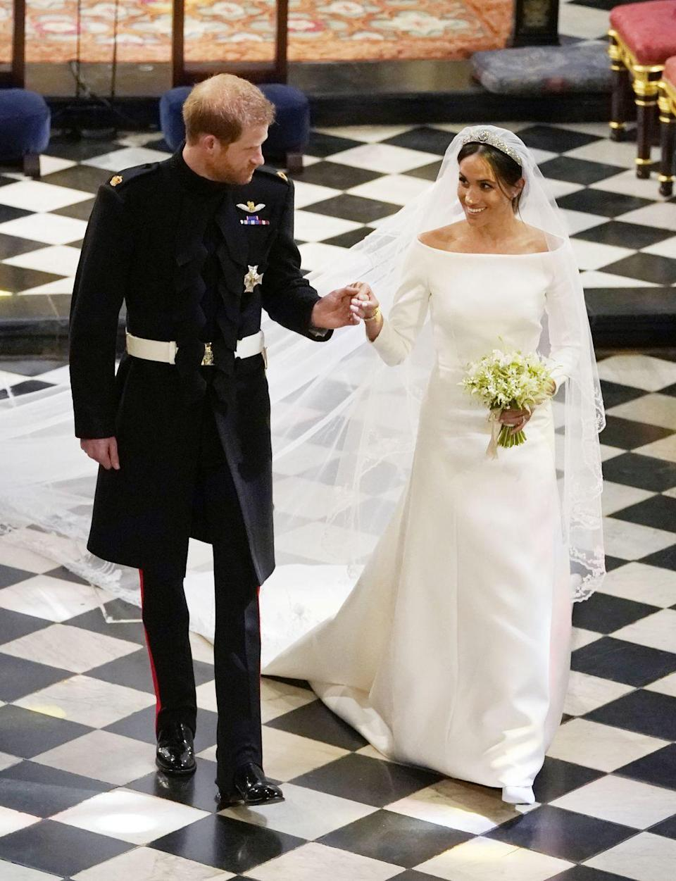 <p>For her royal wedding to Prince Harry, Meghan wore a boat-neck, long-sleeved white dress designed by Clare Waight Keller for Givenchy.</p><p>The veil, in particular, had a symbolic meaning behind it that relates to Prince Harry's appointment as Commonwealth Youth Ambassador. It featured a unique flora from every Commonwealth country, is five metres long and is made from silk tulle with a trim of hand-embroidered flowers.</p><p>The Queen lent Markle Queen Mary's diamond bandeau tiara made in 1932, while the brooch at its centre was created in 1893.</p>