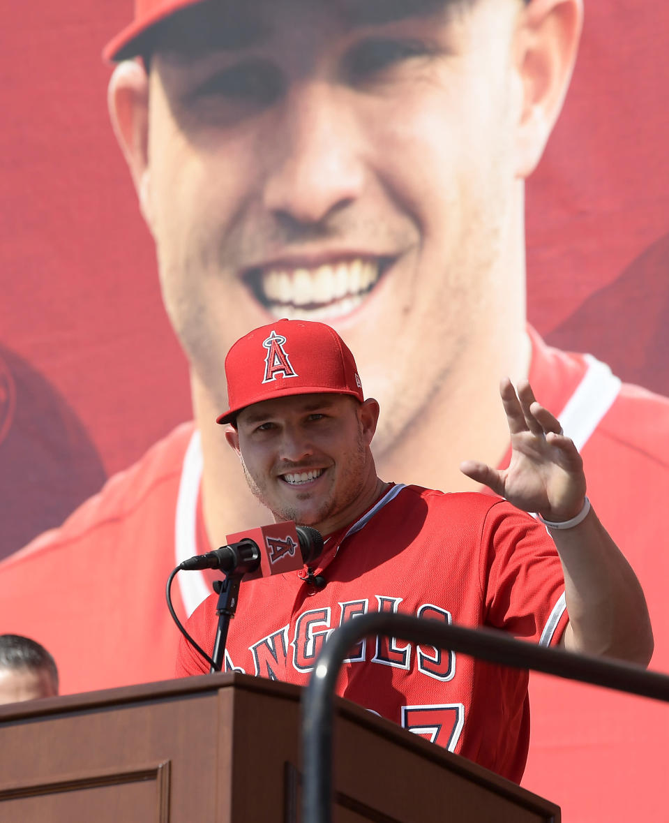 Los Angeles Angels center fielder Mike Trout gestures toward fans during a news conference to talk about his 12-year $426.5 million contract prior to a preseason baseball game against the Los Angeles Dodgers, Sunday, March 24, 2019, in Anaheim, Calif. (AP Photo/Mark J. Terrill)