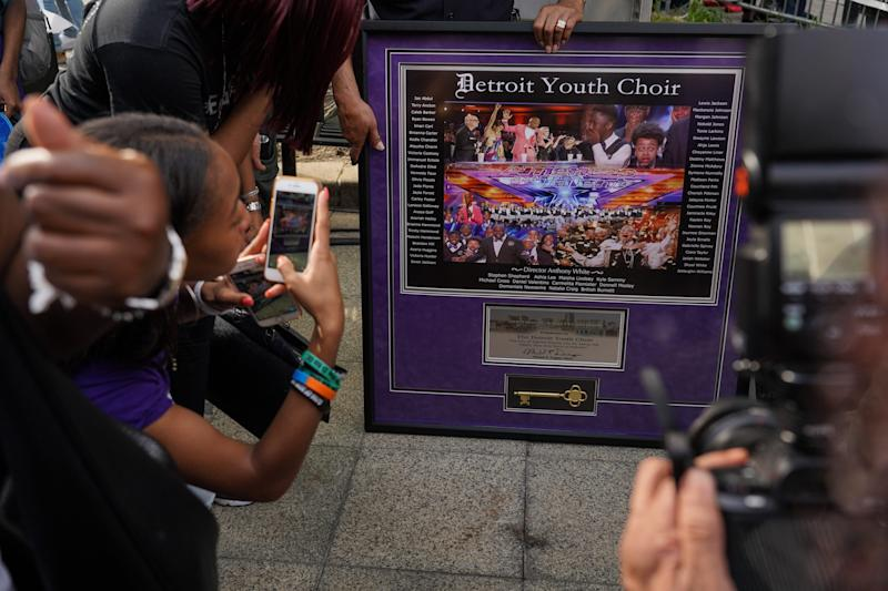 People take photos of the key to the city given to the Detroit Youth Choir during their homecoming celebration at Campus Martius in downtown Detroit on Friday, September 20, 2019 after they finished second place in