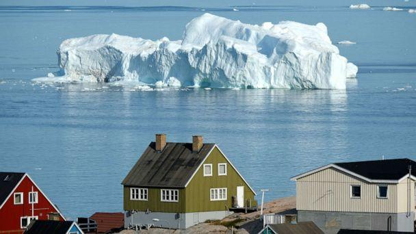 PHOTO: An iceberg floats in Disko Bay behind houses during unseasonably warm weather, July 30, 2019, in Ilulissat, Greenland. (Sean Gallup/Getty Images)