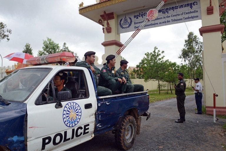 Cambodian police sit in a pick-up truck as they leave the war crimes court in Phnom Penh on September 16, 2012