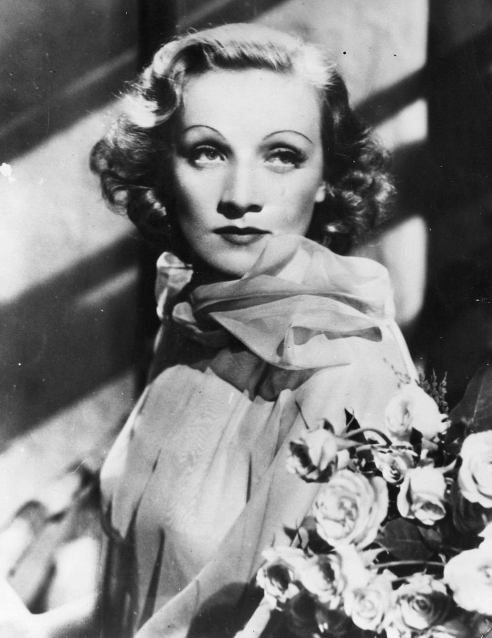 """<p>Marie Magdalene """"Marlene"""" Dietrich was born in 1901 in Berlin, Germany. Her father was a military officer who passed when Dietrich was young, and her and her sister were first tutored at home in ballet, violin, and piano. This musical education inspired the young Dietrich to work towards being a violinist, but a wrist injury in her teenage years kept her from pursuing that path—much to the film industry's benefit. Dietrich began acting in small roles, and eventually landed a part in <em>The Blue </em><em>Angel</em>, which capitulated her to Hollywood. Among her most notable films, especially during the 1930's and 40's, were <em>Shanghai Express</em>, <em>I Love a Soldier</em>, and <em>Manpower</em><em>. </em></p><p>Dietrich, at the onset of World War II, spoke out against the Nazis of her home country and eventually became an American citizen in 1939. Her performances for Allied troops and aid in selling war bonds led to Germany denouncing her, but it is estimated that she helped raise over a million dollars for the war effort. </p><p>The femme fatale, who focused on singing later in her career and was revered for her voice's deep register, was also known for her captivating and alluring personality that led to her many love affairs—with both men and women. Greta Garbo, Frank Sinatra, Mercedes de Acosta, Gary Cooper, and Jimmy Stewart (to name a few) were all counted among her partners. She married Rudolf Sieber (who she met on the set of <em>A Love Tragedy</em>) in 1923, but they were separated for most of their marriage, despite not divorcing until 1976. Many of her writings and journals, recently released by her daughter Maria Riva 25 years following her death, detail her many romantic encounters. Billy Wilder once said that Dietrich was an """"incurably romantic soul"""" and her close friend and confidante Ernest Hemingway famously said, """"If she had nothing more than her voice, she could break your heart with it."""" Dietrich also paved the way for androgynous style—o"""