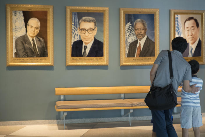 Gen Goto, left, of Tokyo, and his son Motoharu Goto, 9, pause in front of a portrait of former United Nations Secretary-General Kofi Annan during a visit to U.N. headquarters, Saturday, Aug. 18, 2018. Annan, one of the world's most celebrated diplomats and a charismatic symbol of the United Nations who rose through its ranks to become the first black African secretary-general, has died. He was 80. (AP Photo/Mary Altaffer)