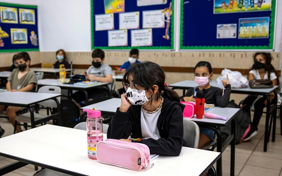 Pupils wear protective face masks to protect against Covid-19, as Israel loosens virus lockdown restrictions and schools are reopened - AP