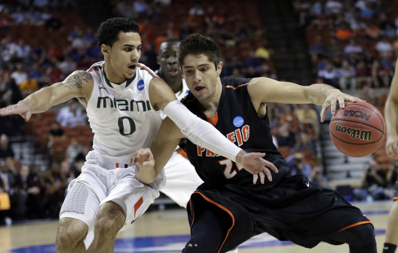 Miami's Shane Larkin (0) tries to steal the ball from Pacific's Rodrigo De Souza during the first half of a second-round game of the NCAA college basketball tournament Friday, March 22, 2013, in Austin, Texas. (AP Photo/Eric Gay)