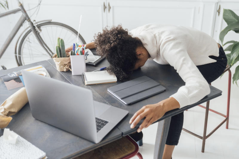 Tired woman with face planted on a desk.