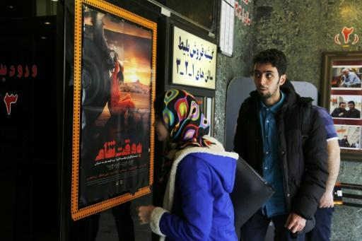 "Iranians buy tickets for the film ""Be Vaght-e Cham"" (""Damascus Time"") by Iranian director Ebrahim Hatamikia at a cinema in Tehran on May 1, 2018"