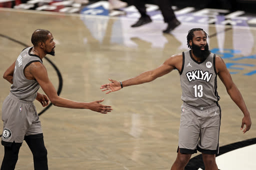 Brooklyn Nets guard James Harden (13) reacts after making a basket with forward Kevin Durant during the second half of an NBA basketball game against the Miami Heat, Monday, Jan. 25, 2021, in New York. (AP Photo/Adam Hunger)