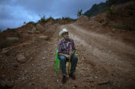 Alejandro Mejia, 80, rests in a chair alongside a dirt road after a visit to the site where the home he built once stood, in the hillside community of La Reina, Honduras, Saturday, June 26, 2021. The home that Mejia and his wife had lived in for 48 years was buried in an epic mudslide triggered by heavy rains brought on by Hurricanes Eta and Iota in November 2020. (AP Photo/Rodrigo Abd)