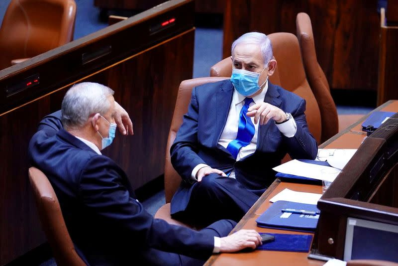FILE PHOTO: Israeli Prime Minister Benjamin Netanyahu and Benny Gantz, wear face masks as they talk during a swearing in ceremony of the new government, at Israel's parliament, in Jerusalem