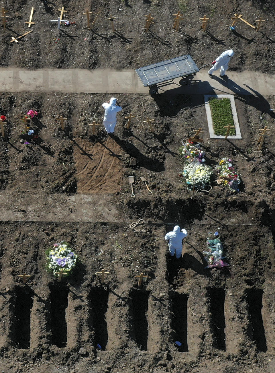 FILE - In this July 25, 2020 file photo, cemetery workers prepare graves at the Flores cemetery where people who died from the coronavirus are being buried in Buenos Aires, Argentina. People are on edge in Argentina, where the number of new coronavirus cases is surging despite nearly five months of strict limits on movement and activities in Buenos Aires and the surrounding area. (AP Photo/Gustavo Garello, File)