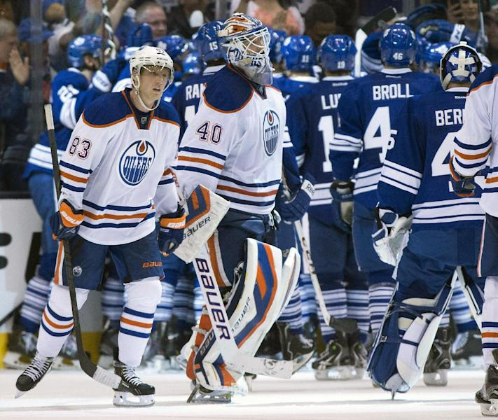 Edmonton Oilers goaltender Devan Dubnyk and right winger Ales Hemsky (83) skate off the ice as the Toronto Maple Leafs celebrate their 6-5 overtime win in an NHL hockey game, Saturday, Oct. 12, 2013 in Toronto. (AP Photo/The Canadian Press, Frank Gunn)