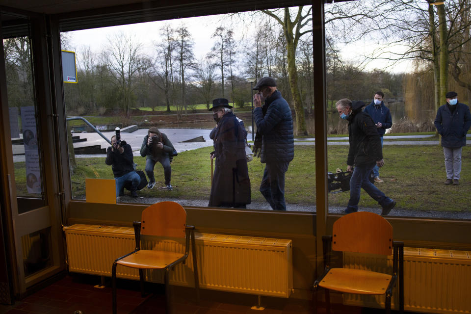 Okko Molenkamp, 94, center left with black hat, is filmed and photographed as he walks to the entrance of a COVID-19 vaccination facility in Apeldoorn, Netherlands, Tuesday, Jan. 26, 2021. Dutch authorities began vaccinating the first of thousands of people aged over 90 years who still live at home. (AP Photo/Peter Dejong)