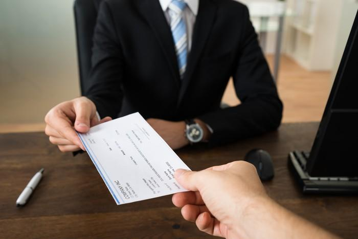 Worker being handed a paycheck.