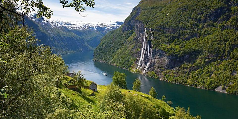 """<p>In a country known for fjords, <a href=""""https://www.tripadvisor.com/Attraction_Review-g642196-d1371544-Reviews-Geiranger_Fjord-Geiranger_Stranda_More_og_Romsdal_Western_Norway.html"""" rel=""""nofollow noopener"""" target=""""_blank"""" data-ylk=""""slk:Geirangerfjord"""" class=""""link rapid-noclick-resp"""">Geirangerfjord</a> is considered the most dazzling. The best way to see this glacial waterway and its multitude of waterfalls cascading down forest-covered mountains (including a famous cluster known as the """"Seven Sisters"""") is to take a scenic cruise. You can also go kayaking, biking, or hiking, and even a helicopter tour is an option. </p>"""