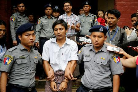 FILE PHOTO: Detained Reuters journalist Kyaw Soe Oo and Wa Lone are escorted by police as they leave after a court hearing in Yangon, Myanmar, August 20, 2018. REUTERS/Ann Wang/File Photo