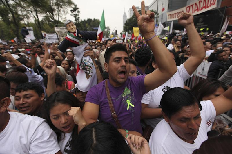 Supporters of former presidential candidate Andres Manuel Lopez Obrador cheer as they listen to Lopez Obrador during an act to protest against the government's proposed energy reforms that would allow private companies to explore the country's oil and gas reserves, in Mexico City, Sunday Sept. 8, 2013. The proposed reform requires constitutional changes that strike at the heart of one of Mexico's proudest moments: President Lazaro Cardenas' nationalization of the oil company in 1938. (AP Photo/Marco Ugarte)