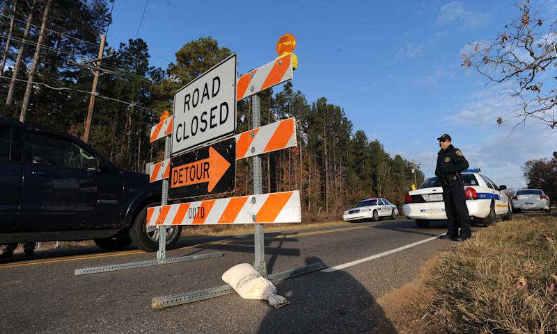 Law enforcement personnel stand at a roadblock along Hwy 163 just south of Doyline, La., Saturday Dec. 1, 2012. Authorities have begun moving 1 million pounds of improperly stored explosive powder to storage bunkers at the Camp Minden industrial site. State investigators found the explosives while inspecting property leased by Explo Systems, where an above-ground storage magazine exploded in October. (AP Photo/The Shreveport Times, Jim Hudelson) MAGS OUT; MANDATORY CREDIT SHREVEPORTTIMES.COM; NO SALES