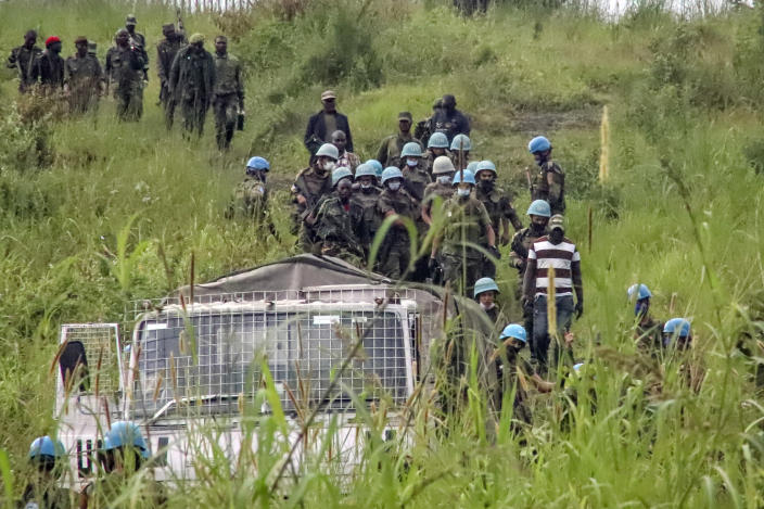 United Nations peacekeepers recover bodies from an area near the site where a U.N. convoy was attacked in Nyiragongo, North Kivu province, Congo, on Monday, Feb. 22, 2021. Luca Attanasio, Italian ambassador to the Congo, an Italian Carabineri bodyguard and a Congolese driver were killed in the area that is home to myriad rebel groups, according to the Foreign Ministry and local people. (AP Photo/Justin Kabumba)