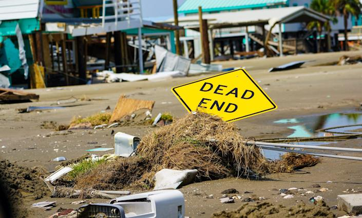 A street sign was knocked almost flat, covered in march vegetation and sand, during the passage of Hurricane Ida on Grand Isle, Louisiana.