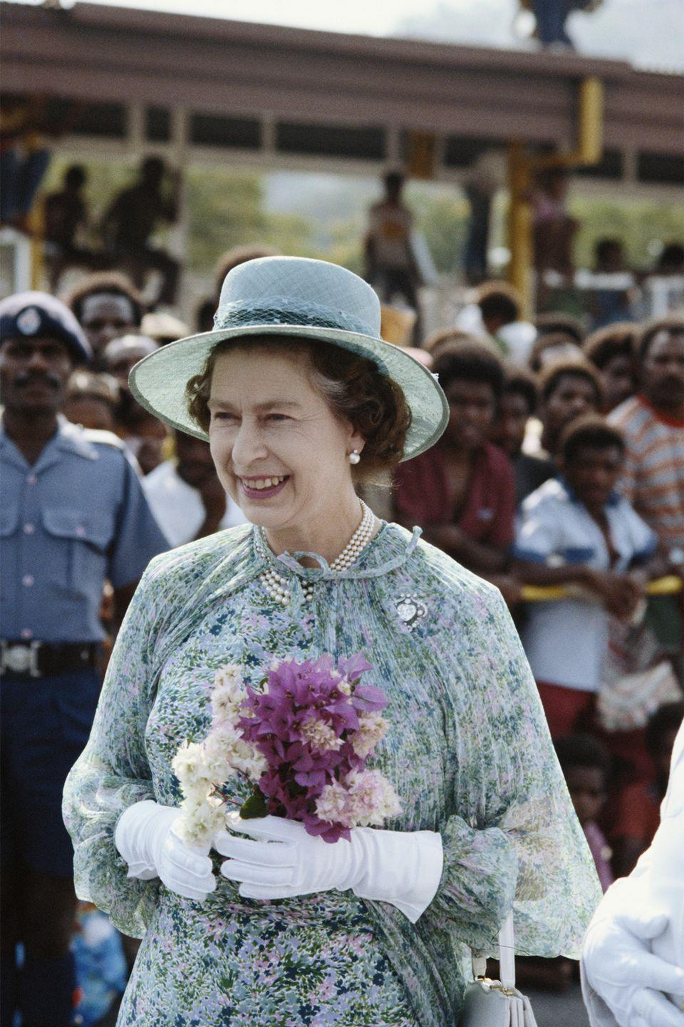 <p>Elizabeth wears a blue floral ensemble while holding a bouquet for a royal trip to Port Moresby, Papua New Guinea.<br></p>